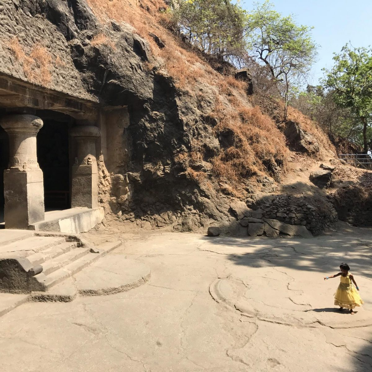 A girl plays at a temple carved out of rock
